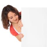 Junge Frau, die hinter unbelegtem Zeichen steht Stockfoto