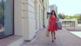 Junge Frau, die hinunter die Straße mit Einkaufstaschen geht stock video footage