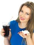 Junge Frau, die hohen Sugar Fizzy Drink trinkt stockbild