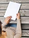 Junge Frau, die am Holztisch mit einer Broschüre mit weißer Abdeckung sitzt Stockbild