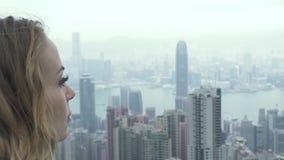 Junge Frau, die Hong Kong-Stadtpanorama von Höchst-Victoria schaut Aufpassender Panoramablick der touristischen kaukasischen Frau stock video