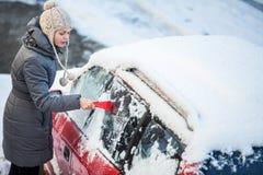Junge Frau, die ihr Auto vom Schnee und vom Frost säubert Stockfotos