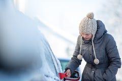 Junge Frau, die ihr Auto vom Schnee und vom Frost säubert Stockbilder