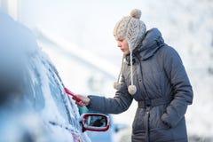 Junge Frau, die ihr Auto vom Schnee und vom Frost säubert Lizenzfreies Stockbild
