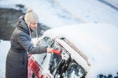 Junge Frau, die ihr Auto vom Schnee und vom Frost säubert Stockfotografie