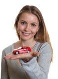 Junge Frau, die ihr erstes Auto darstellt stockbilder