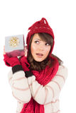 Junge Frau, die ihr Geschenk rüttelt, um zu schätzen, was es ist Stockbilder
