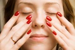 Junge Frau, die ihr Gesicht berührt lizenzfreies stockbild