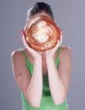 Junge Frau, die ihr Gesicht hinter einem runden Brötchen versteckt Lizenzfreie Stockfotos