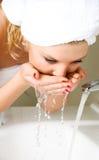Junge Frau, die ihr Gesicht wäscht stockbild