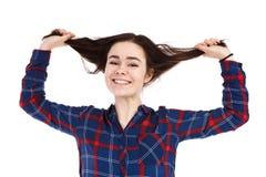 Junge Frau, die ihr Haar auf weißem Hintergrund zieht Stockfotos