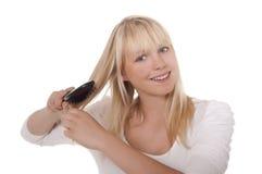 Junge Frau, die ihr Haar kämmt Stockbilder
