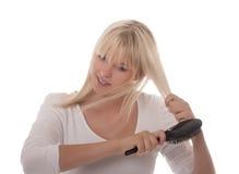 Junge Frau, die ihr Haar kämmt Lizenzfreie Stockfotos