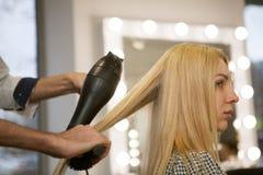 Junge Frau, die ihr Haar vom Friseur anreden lässt stockbild