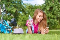 Junge Frau, die ihr intelligentes Telefon am Park verwendet Lizenzfreies Stockbild