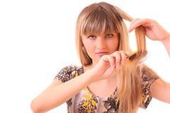 Junge Frau, die ihr langes blondes Haar tut Stockfoto