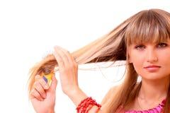 Junge Frau, die ihr langes blondes Haar tut Lizenzfreies Stockbild
