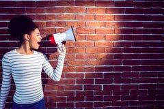Junge Frau, die ihr Megaphon im Licht verwendet Stockbilder