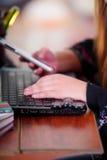 Junge Frau, die ihr Mobiltelefon im Büro und ein populäres Unruhespinnerspielzeug über dem Laptop, auf Bürohintergrund verwendet Stockfoto