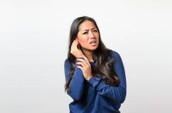 Junge Frau, die ihr schmerzliches Ohr hält lizenzfreie stockfotografie