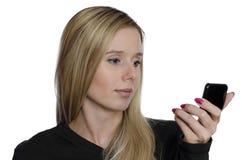 Junge Frau, die ihr Selbst im kleinen schwarzen Spiegel auf weißem Hintergrund betrachtet Stockbild