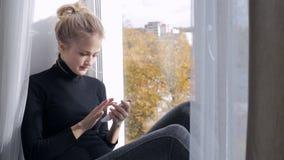 Junge Frau, die ihr Smarttelefon sitzt auf Fensterbrett verwendet stock footage