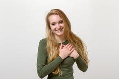 Junge Frau, die ihr tief empfunden Dankbarkeit zeigt stockfotografie