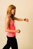 Junge Frau, die ihre Apple-Uhr beim Rütteln überprüft Stockfoto