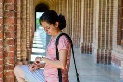 Junge Frau, die ihre Armbanduhr betrachtet lizenzfreies stockfoto