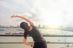 Junge Frau, die ihre Arme auf Pier im Sommer ausdehnt Lizenzfreie Stockbilder