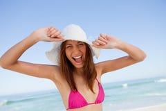 Junge Frau, die ihre Arme im Glück vor dem Meer anhebt Stockfoto