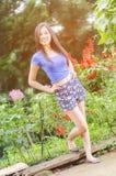 Junge Frau, die ihre Arme und Lächeln zu Ihnen, grüner Hintergrund der Natur anhebt lizenzfreies stockbild