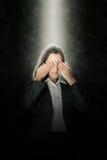 Junge Frau, die ihre Augen in einem Strahl des Lichtes bedeckt Lizenzfreies Stockbild