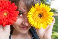 Junge Frau, die ihre Augen mit frischen bunten Blumen bedeckt enjoy Lizenzfreie Stockfotos