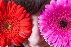 Junge Frau, die ihre Augen mit frischen bunten Blumen bedeckt Makro Stockbilder