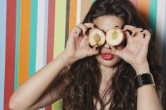 Junge Frau, die ihre Augen mit Pfirsich gegen gestreiften Hintergrund bedeckt Lizenzfreies Stockbild