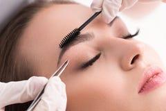 Junge Frau, die ihre Augenbrauen im Schönheitssaal auszupft Stockfotografie