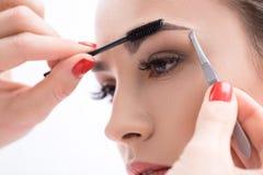 Junge Frau, die ihre Augenbrauen im Schönheitssaal auszupft Lizenzfreies Stockbild