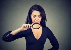 Junge Frau, die ihre Brüste durch Lupe betrachtet Lizenzfreies Stockfoto