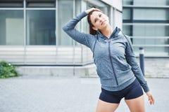 Junge Frau, die ihre Muskeln ausdehnt stockfoto