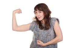 Junge Frau, die ihre Muskeln biegt Stockfoto
