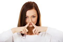 Junge Frau, die ihre Nase wegen eines schlechten Geruchs hält stockbild