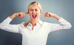 Junge Frau, die ihre Ohren blockiert Stockfotos