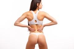 Junge Frau, die ihre schmerzliche Rückseite berührt Lizenzfreie Stockfotografie