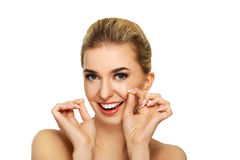 Junge Frau, die ihre Zähne flossing ist stockbild