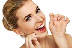 Junge Frau, die ihre Zähne flossing ist lizenzfreie stockfotografie