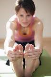 Junge Frau, die ihre Zehen berührt Stockfotos
