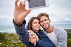 Junge Frau, die an ihrem Freund beim Nehmen eines selfie lächelt lizenzfreie stockfotos