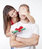 Junge Frau, die ihrem Freund eine Überraschung vorhanden gibt Stockfoto