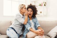 Junge Frau, die ihrem Freund einigen Geheimnissen sagt Stockbilder